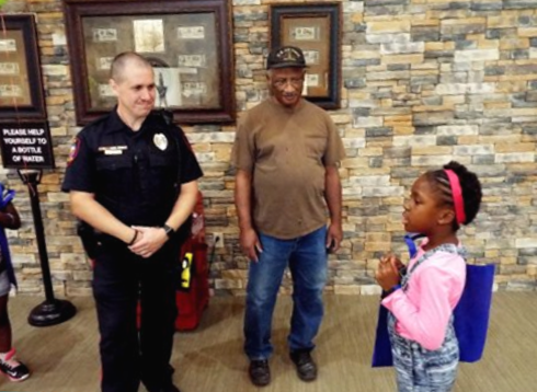 police officer and military veteran talking with little girl