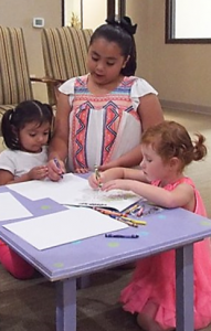 hispanic woman and two little girls at a table