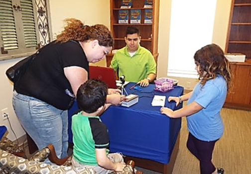 mom and kids signing up at a table