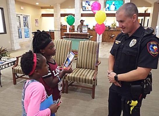 police officer speaking with 2 children