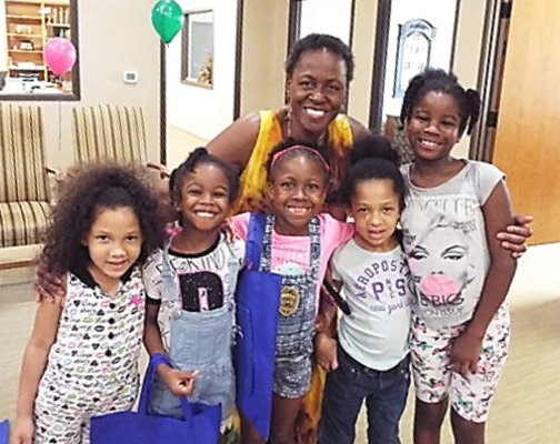 african american woman and 5 kids smiling for the camera