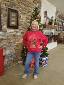 young lady in red sweater in front of the Christmas tree posing for a picture