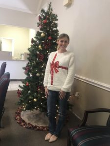 young lady posing in front of Christmas tree